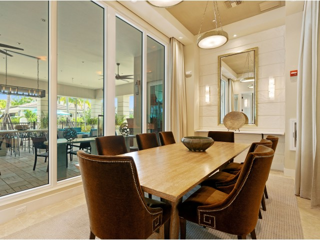 Conference room with large wooden table, 8 chairs and large windows with view to outdoor open-air lounge