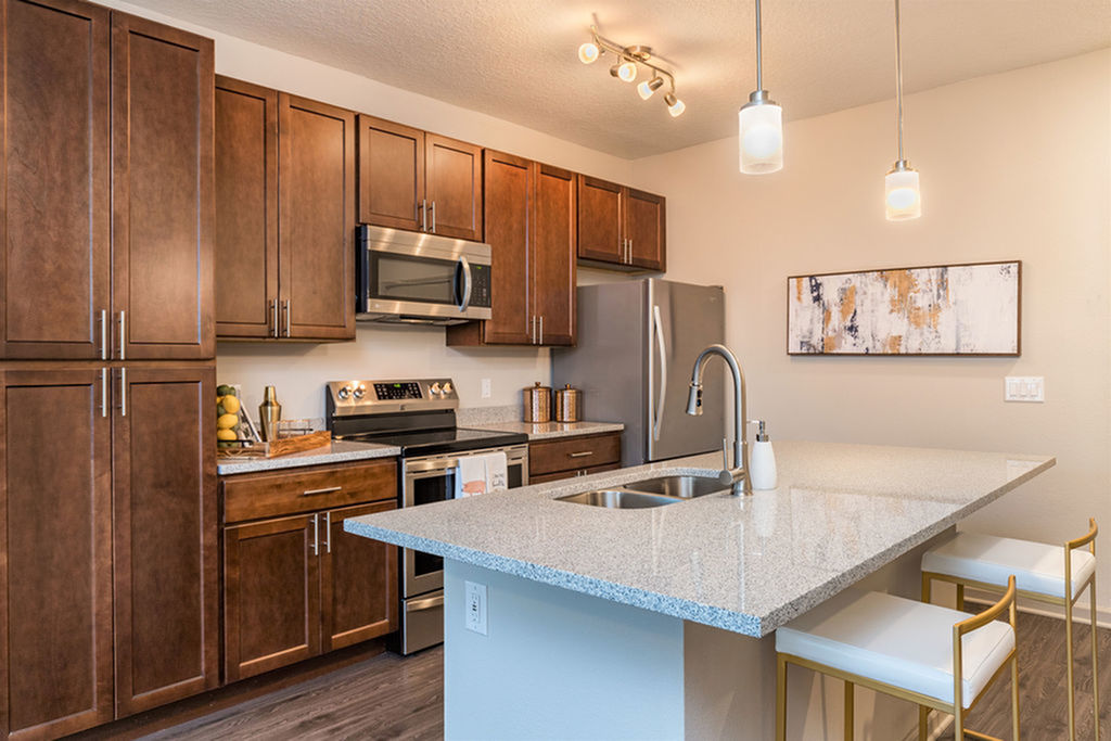 San Mateo Apartments Kissimmee Florida island kitchen with stainless steel appliances, granite counters, undermount sink in island, pendantand track lights, and vinyl plank flooring