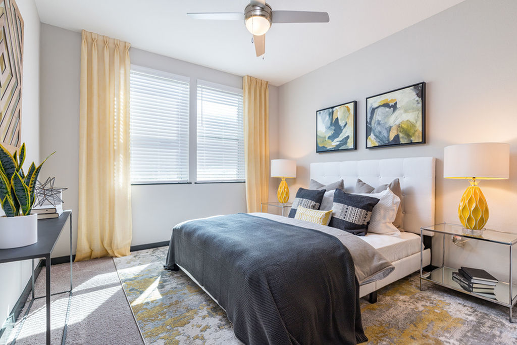 View of furnished model bedroom with carpeting and ceiling fan