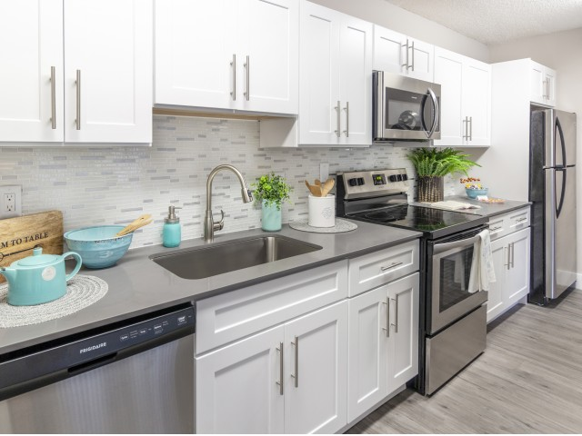 Upgraded kitchen with tile back splash, stainless steel dishwasher, microwave, oven, and refrigerator