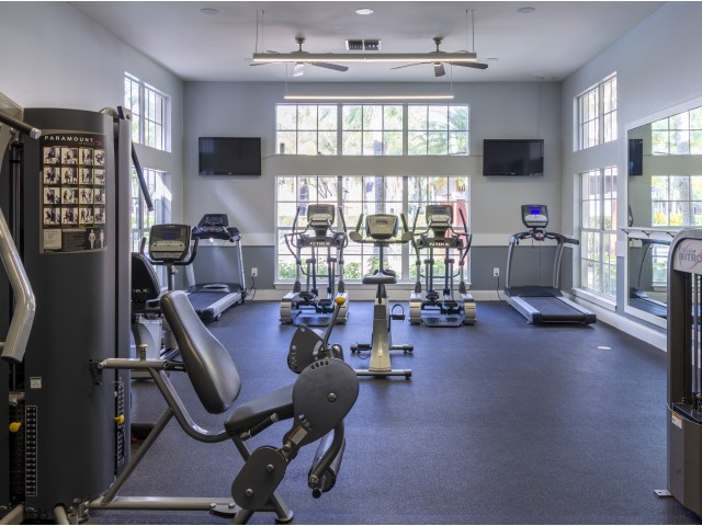 Fitness center with floor to ceiling windows, weight machines, treadmills, ellipticals, and ceiling fans