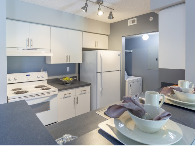 Kitchen with white refrigerator, oven, and full sized laundry