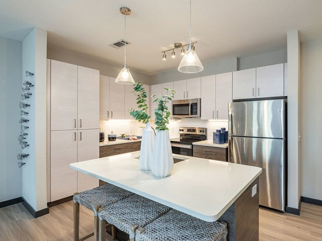 Furnished model kitchen with modern cabinets, stainless appliances, overhead lighting, undercounter lighting, wood plank flooring