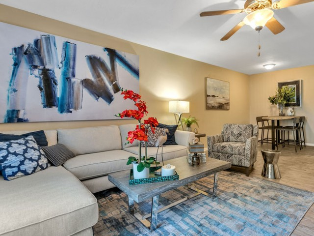 the dunes Indian harbour beach florida furnished model living room with wood plank floors,ceiling fan with lights, adjacent to dining room