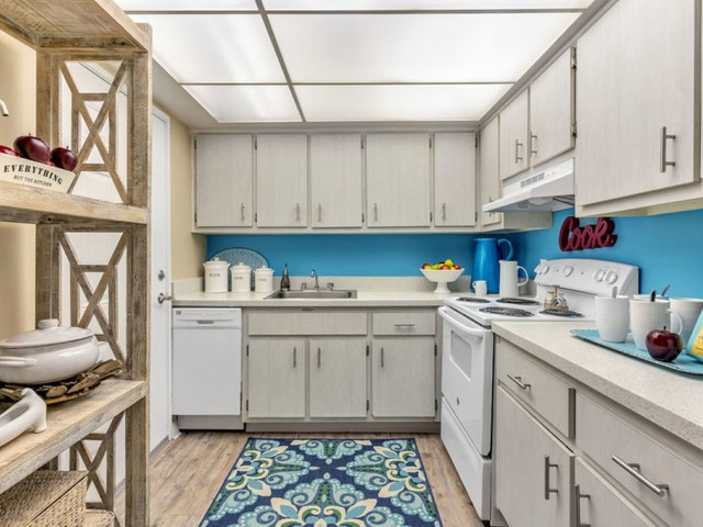 the dunes Indian harbour beach florida furnished kitchen with light cabinetry with modern pulls, wood-plank floors, white appliances, and abundant overhead lighting