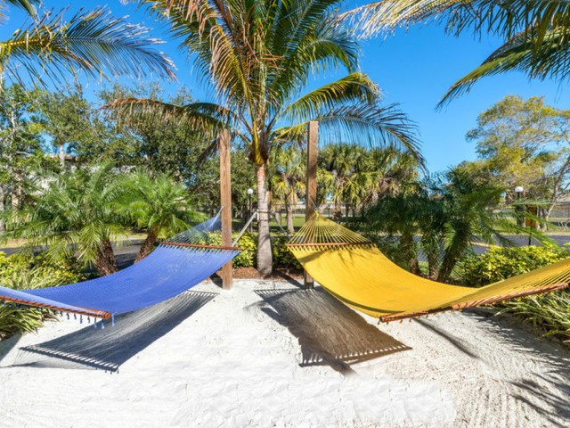 Harbour Pointe Indian Harbour Beach Florida two hammocks hanging under palm trees with sand beneath