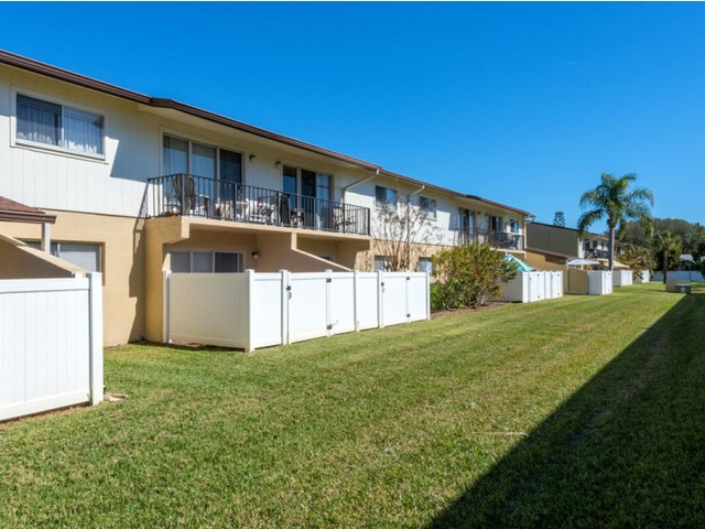 Harbour Pointe Indian Harbour Beach Florida building rear facing area with fenced patio and balcony with grass area
