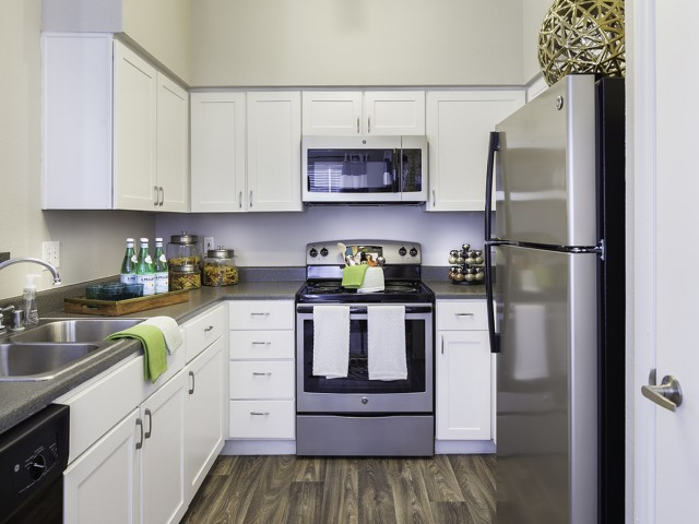 Kitchen with stainless steel appliances, built-in microwave and breakfast bar at The Brixton Apartments in Dallas, TX