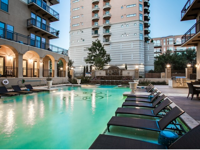 Image of FLOAT: Resort-style pool and courtyard area with water features and fireplace for Cantabria at Turtle Creek Apartments