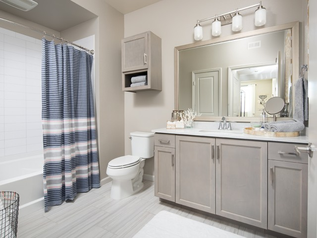 Image of Lavish bathrooms with tile flooring, framed vanity mirror, quartz counters and tile bath surround for Valentia Apartment Homes