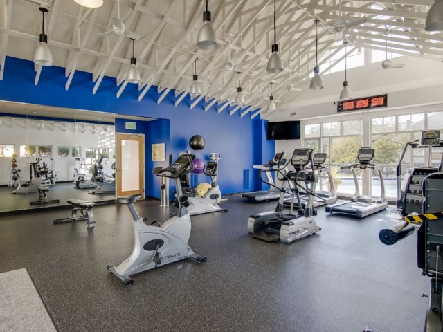 Fitness center with high ceiling with ellipticals, treadmills, stationary bikes, and free weights.