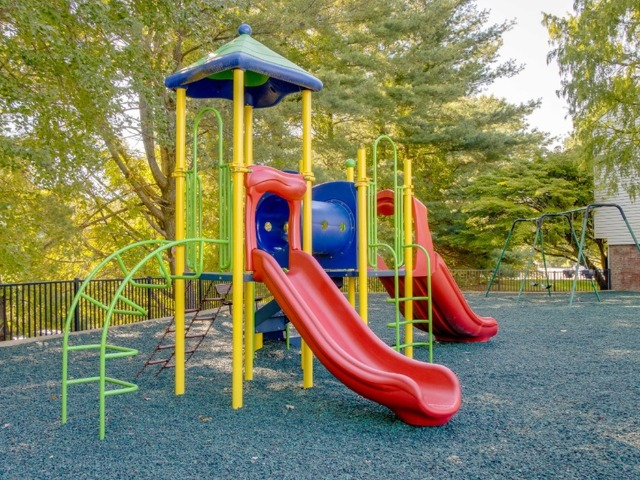 Playground with multiple slides and pieces for climbing.