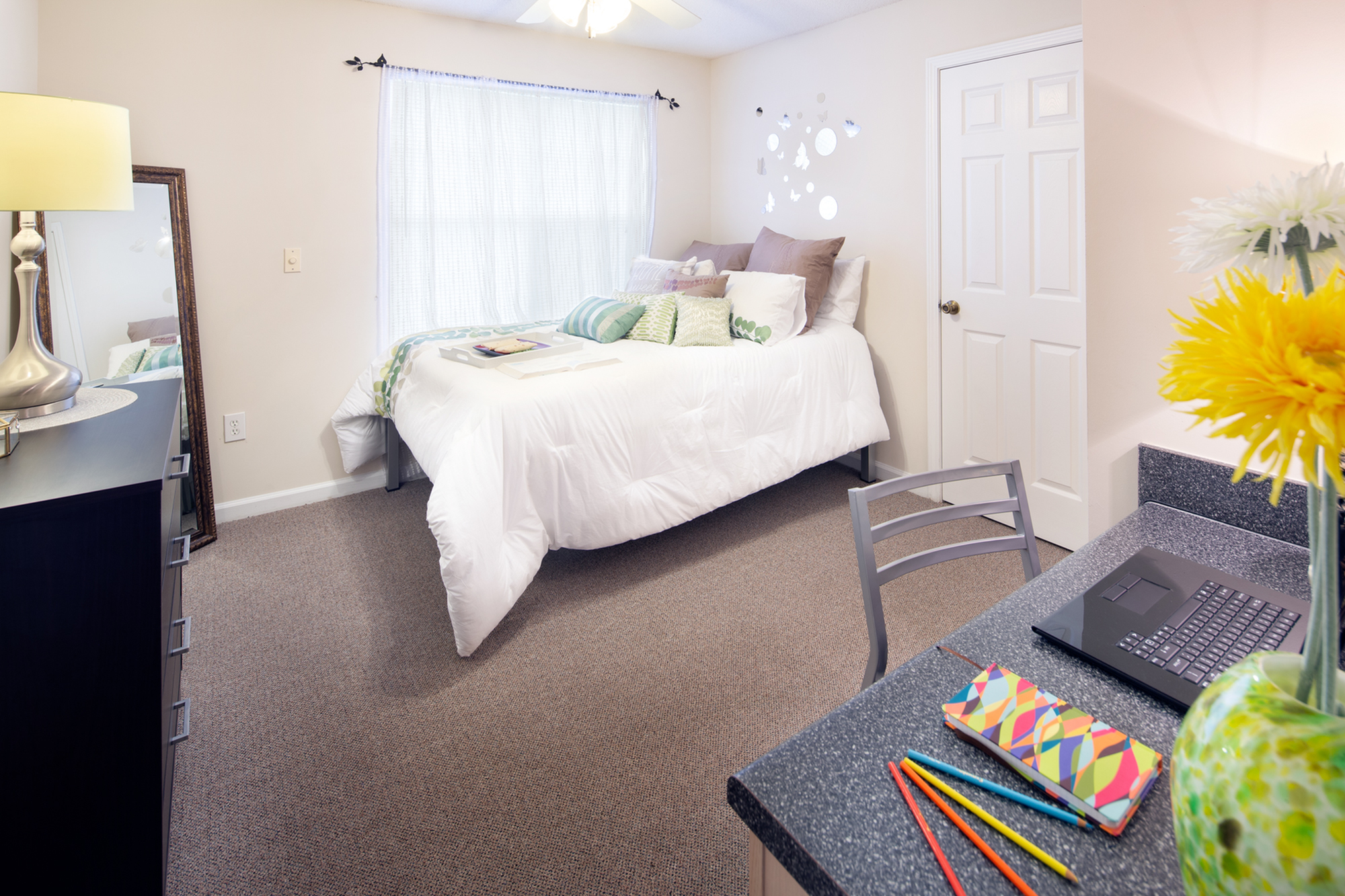 furnished bedroom with bed, dresser, desk, curtains, and spacious closet