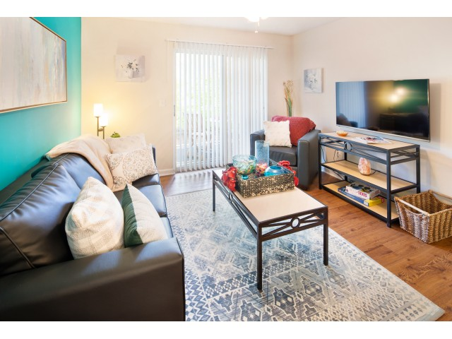 Living space with a 50 inch wall mounted flat-screen TV, couch, chair, tables, sliding glass door, and ceiling fan at The Reserve at Athens