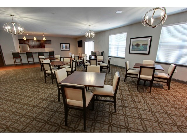 Carlton Hollow Apartments, interior, community lounge, several tables, kitchen area