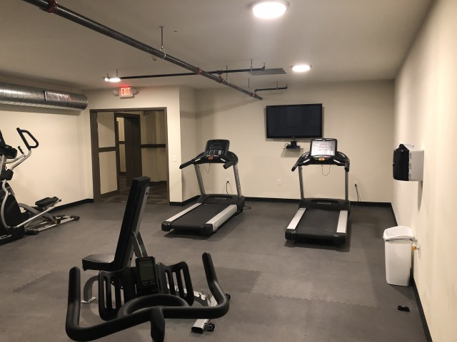 Draper Lofts Apartments, interior, fitness center, treadmills, elliptical, tv