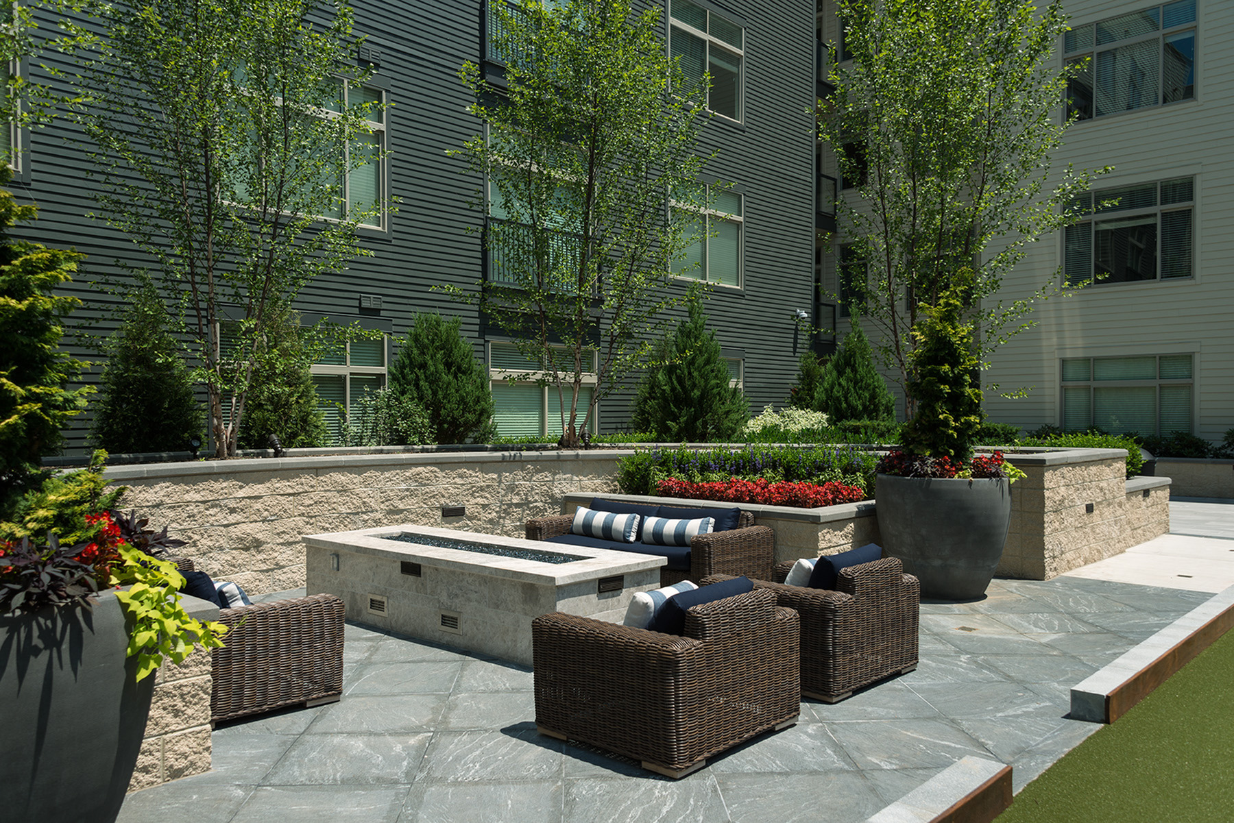 Two landscape courtyards with fireplaces, dining, and grilling stations at Hanover North Broad