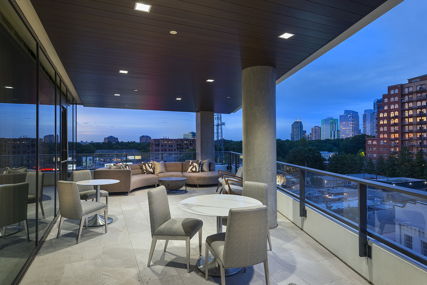 Open-air loggia with dining areas and Skyline views at Hanover Buckhead Village