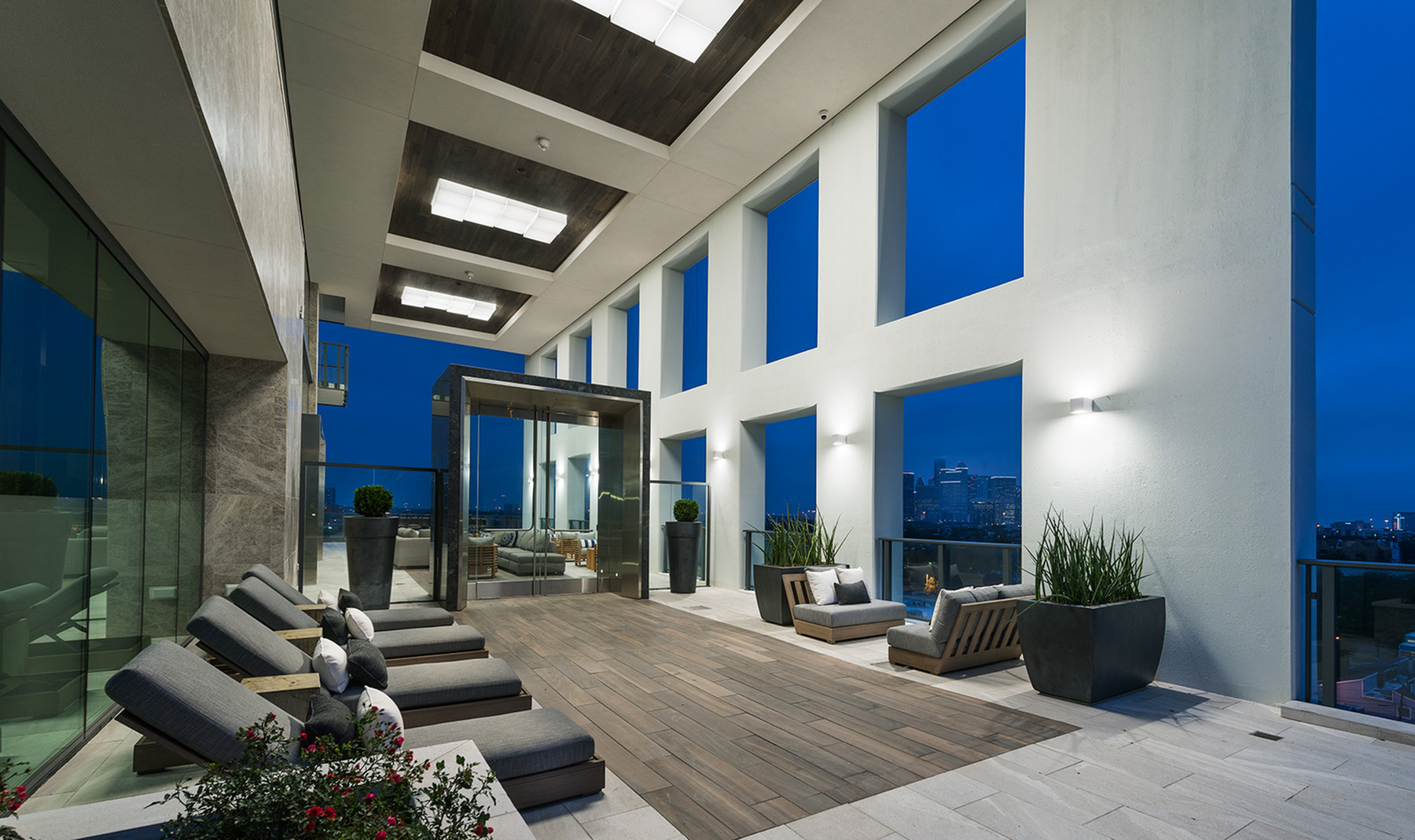 Open-air loggia with dining areas and skyline views at Hanover Montrose