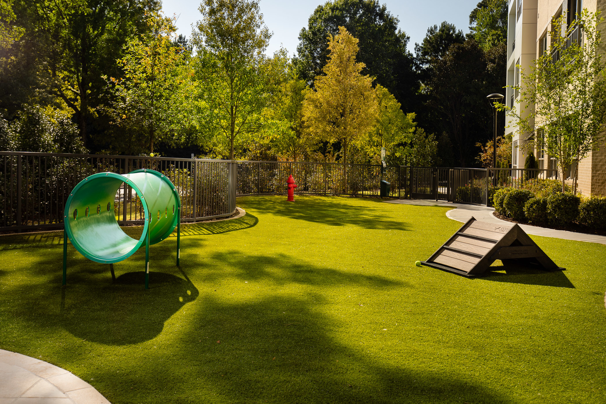 Pet-friendly living featuring a pet spa and oversized pet play park with outdoor seating at Hanover The LINC Brookhaven