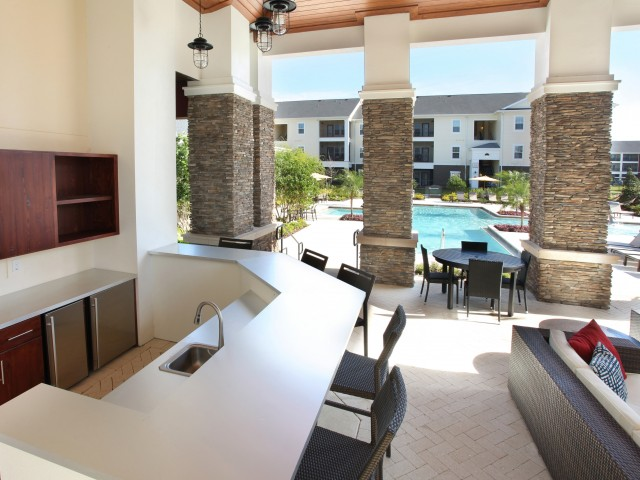 Outdoor summer kitchen with bar seating | The Village at Terra Bella