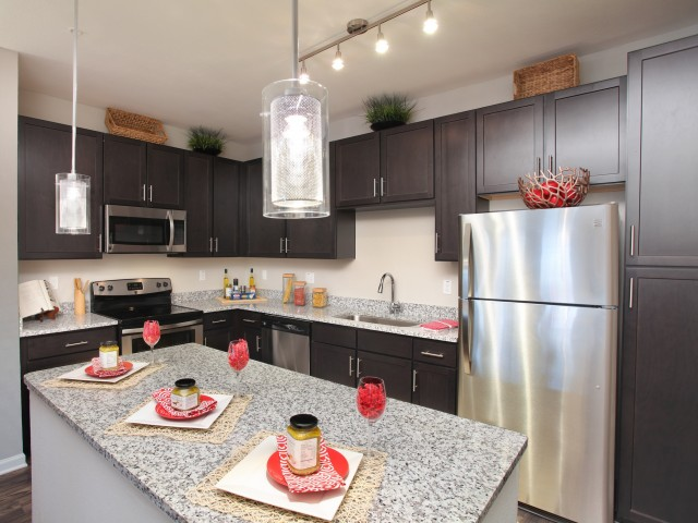 Kitchen with espresso cabinets, granite countertops and stainless steel appliances including built-in microwave