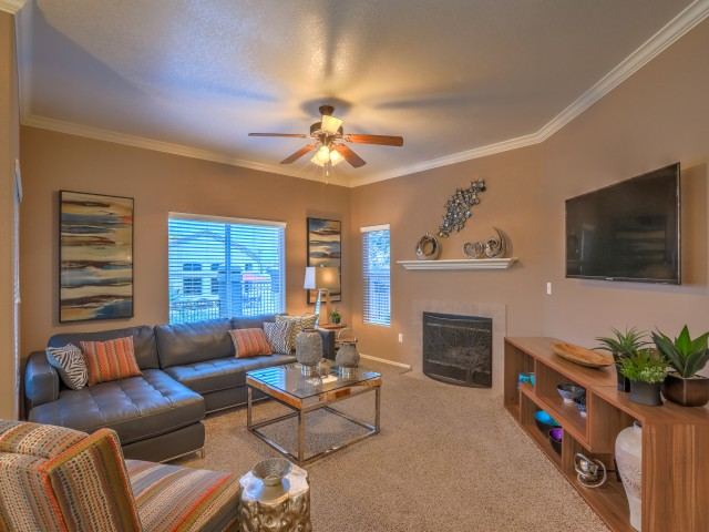 Living room with carpeted flooring, fireplace, crown molding and ceiling fan | Arterra rental homes