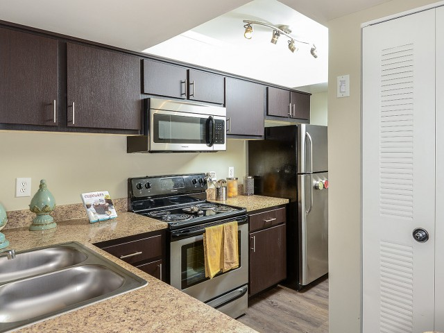 Kitchen with hardwood floors, stainless steel appliances, built in microwave, espresso cabinets | Village Place apartment homes
