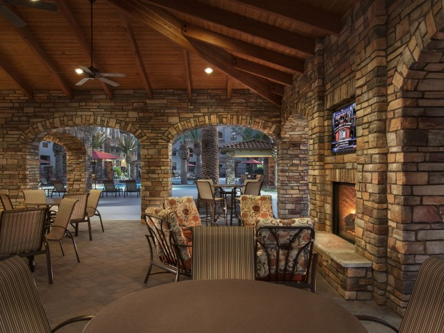 Poolside fireplace with seating and flat screen tv | Tucson AZ apartments | Villas at San Dorado