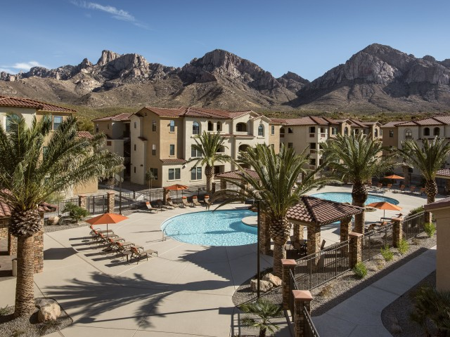 Aerial view of lagoon pool and lounge chairs at Villas at San Dorado apartment complex in Tucson AZ