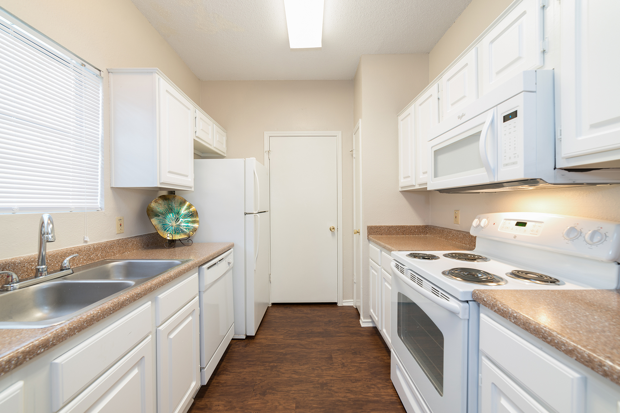 Kitchen with white cabinets and appliances | Canyon Creek apartment