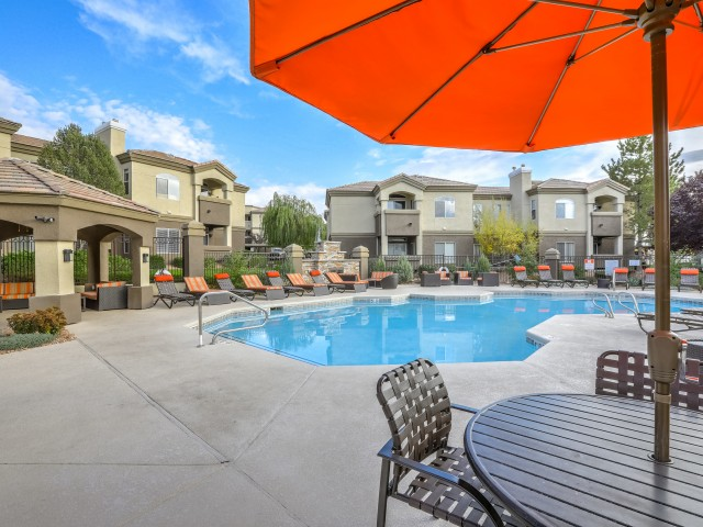 Apartment community pool with lounge chairs and table with umbrella