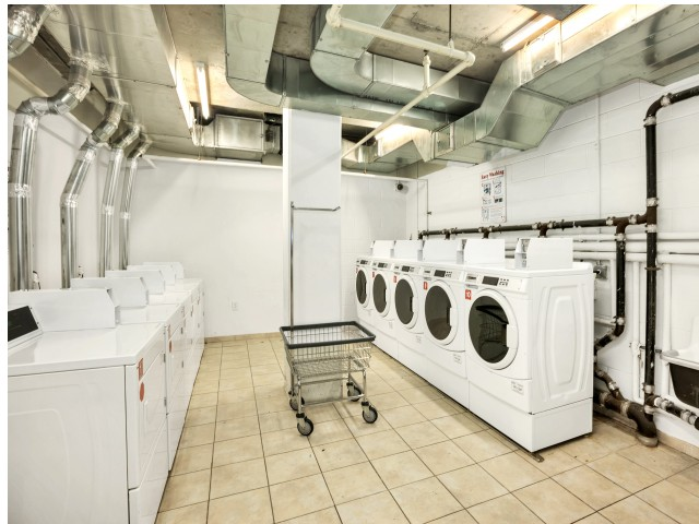 Arabella 101, interior, laundry facility, cart, white washers and dryers, tile floor, vent ducts