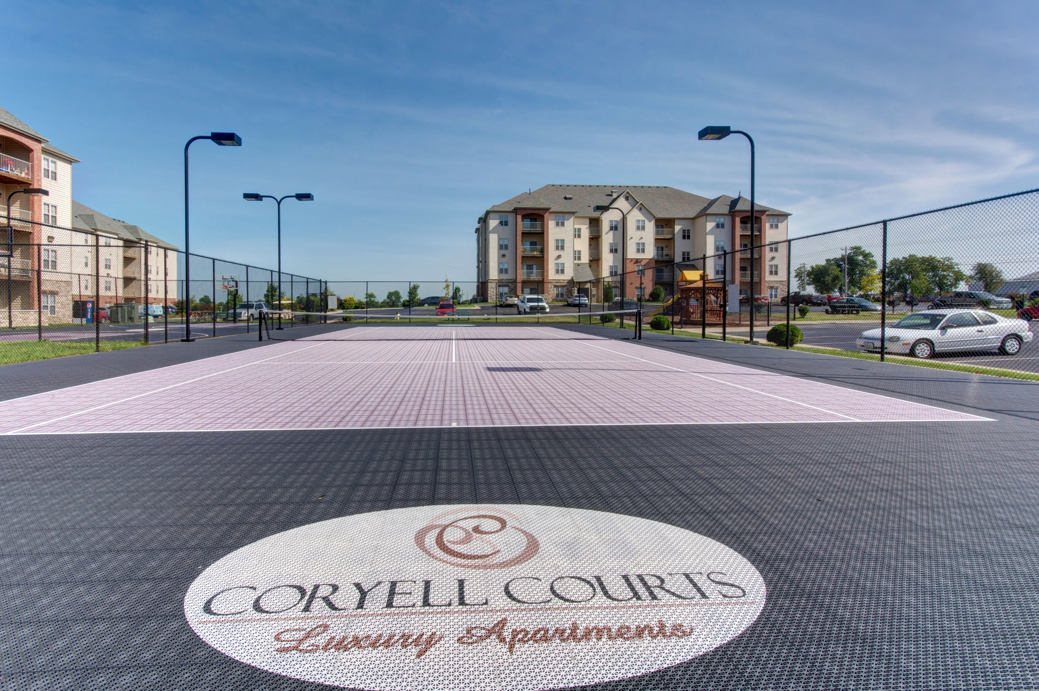 Coryell Courts Apartments amenity tennis court overlooking the exterior apartment building