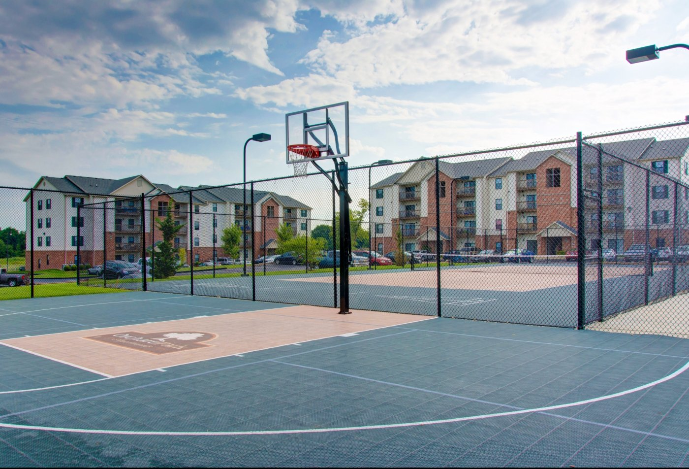 fenced in basket ball and tennis quarts with the Orchard Park Apartments logo on courts