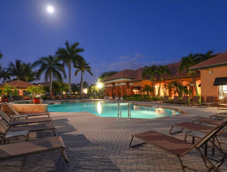 Palms of Monterrey, exterior, night, sparkling blue swimming pool, lounge chairs, clubhouse, palm trees