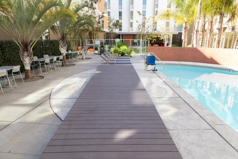 A view from the pool decking facing toward the residential building, but showing the ADA pool assist device, lounge chairs and seating areas.