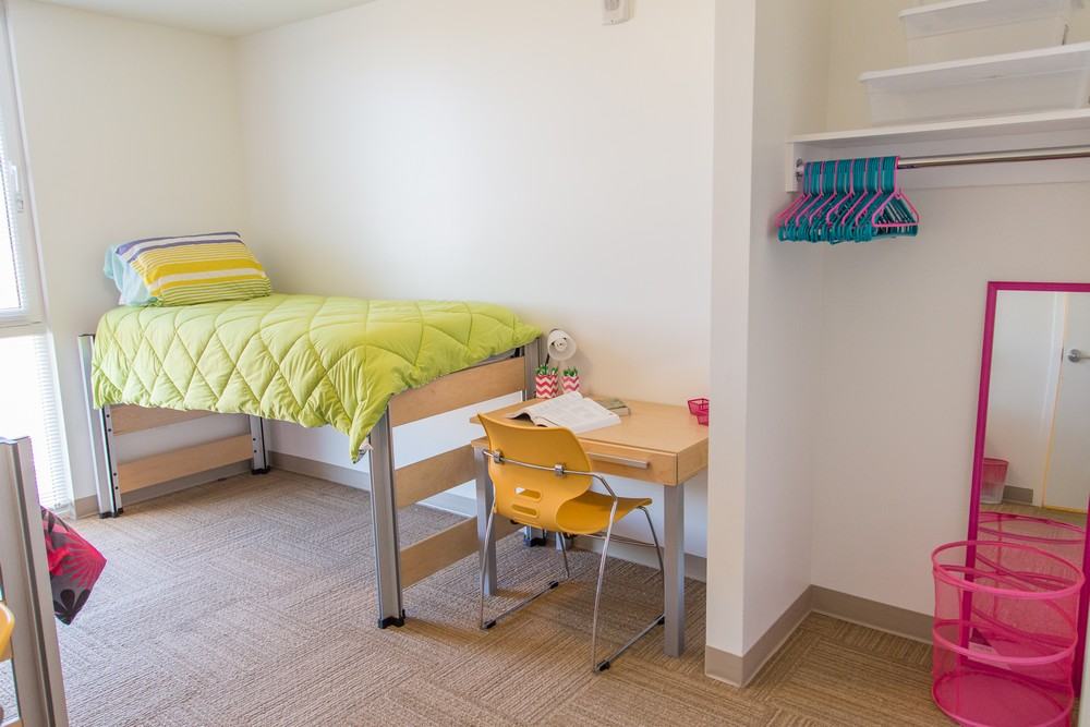 A view of one of two beds in an apartment bedroom with the bed semi-lofted and a student desk at the end with a bright yellow desk chair. The closet can also be seen with a pink laundry basked and mirror, as well as the hanger rod, hangers