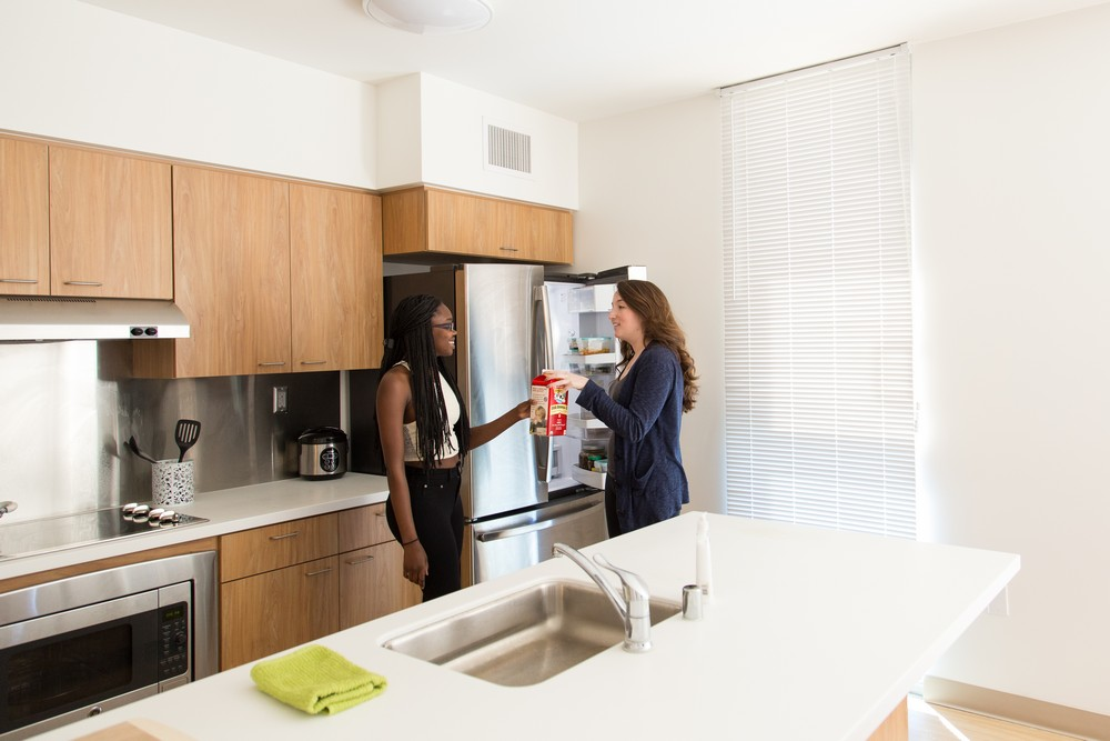 Two residents of an apartment talking in front of an open refrigerator passing a carton of milk between them. The kitchen sink can be seen on the island, along with light oak cabients, and stainless stove, over and vent hood in the backgrou