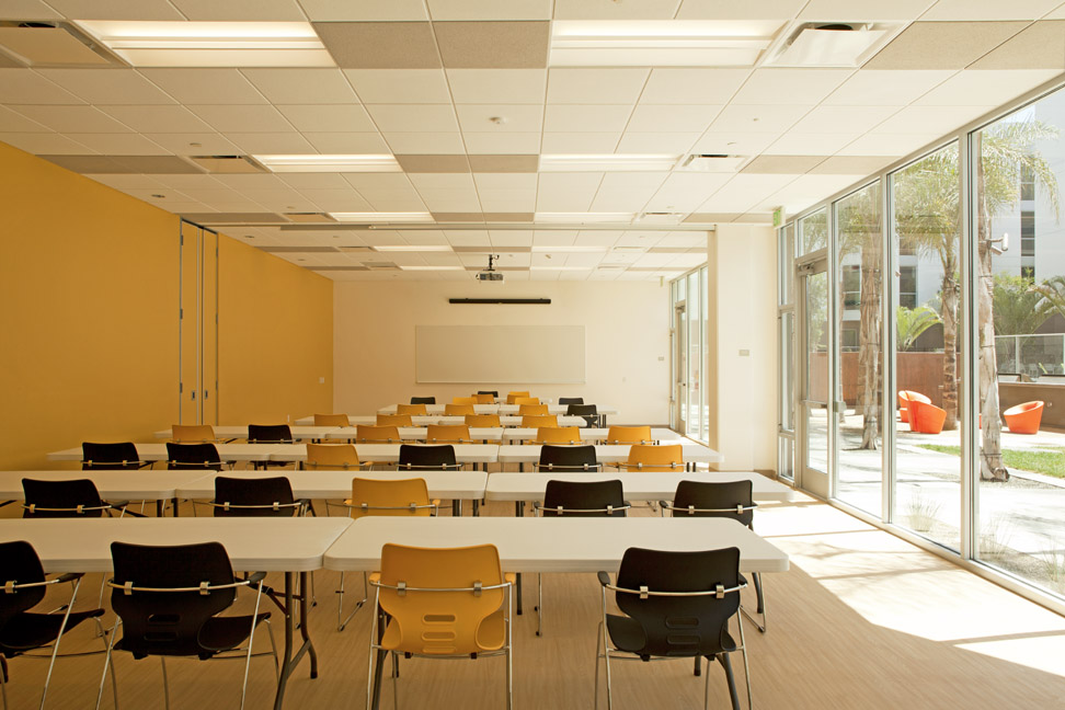 A view of the large classroom from the back facing the screen. The classroom also looks out to the courtyard through floor to ceiling windows o the right.